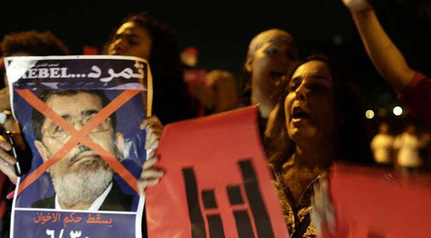 Opponents of Egypt's Islamist president Mohammed Morsi protest outside the defence ministry in Cairo (AP)