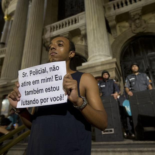"A man holds a message that reads in Portuguese; ""Officer, don't shoot at me. I'm also fighting for you"" during a protest in Rio de Janiero (AP)"
