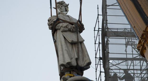The monument of Christopher Columbus, located behind the government house, hangs from a crane as it is removed (AP)