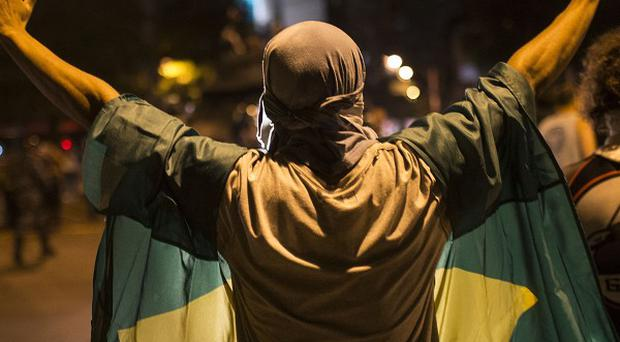 A protester wearing a Brazilian flag holds his hands up as he faces police officers near the Maracana stadium in Rio de Janeiro (AP)