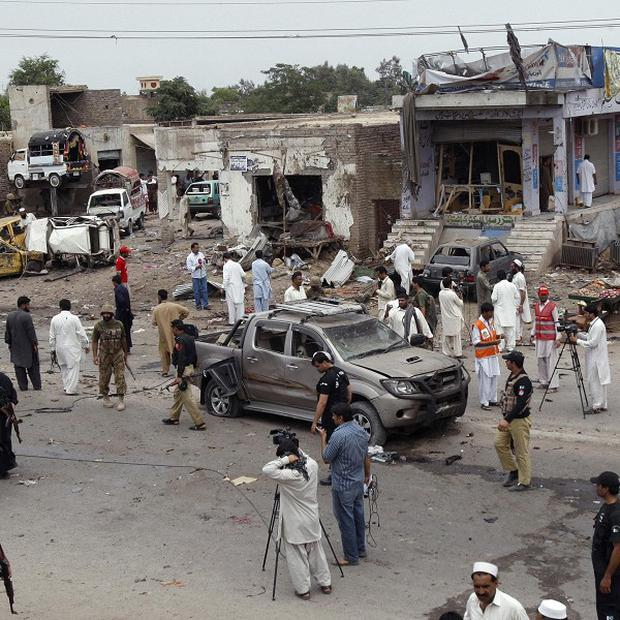 Pakistani security officials at the site of a car bombing on the outskirts of Peshawar (AP)