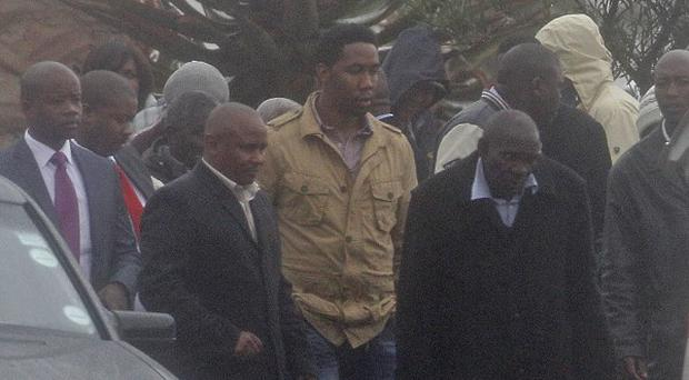Ndaba Mandela, centre, grandson of Nelson Mandela walks with family members at the funeral in Qunu, South Africa (AP)