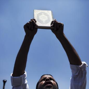 A supporter of ousted president Mohammed Morsi holds a Quran while chanting slogans supporting Morsi during a rally in Cairo University (AP)