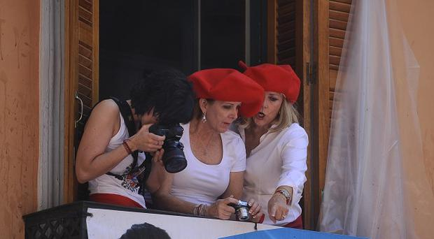 Revelers wearing red Basque berets, look on from a balcony in Ayuntamiento square in Pamplona, northern Spain (AP)