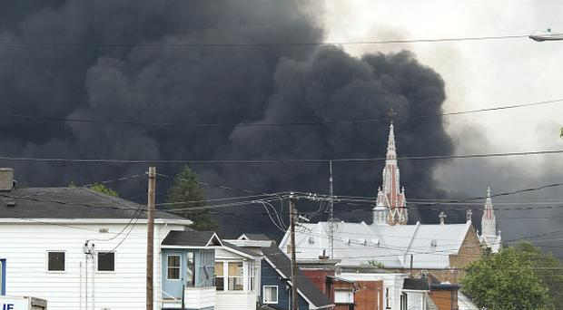 Smoke rises from railway wagons that were carrying crude oil after derailing in downtown Lac Megantic, Quebec, Canada (AP)