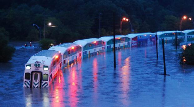 A train is stranded on flooded tracks in Toronto following a severe thunderstorm (AP/The Canadian Press, Winston Neutel)