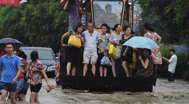 Residents are evacuated through a flooded street by an excavator in Guanghan city in south-western China's Sichuan province (AP)