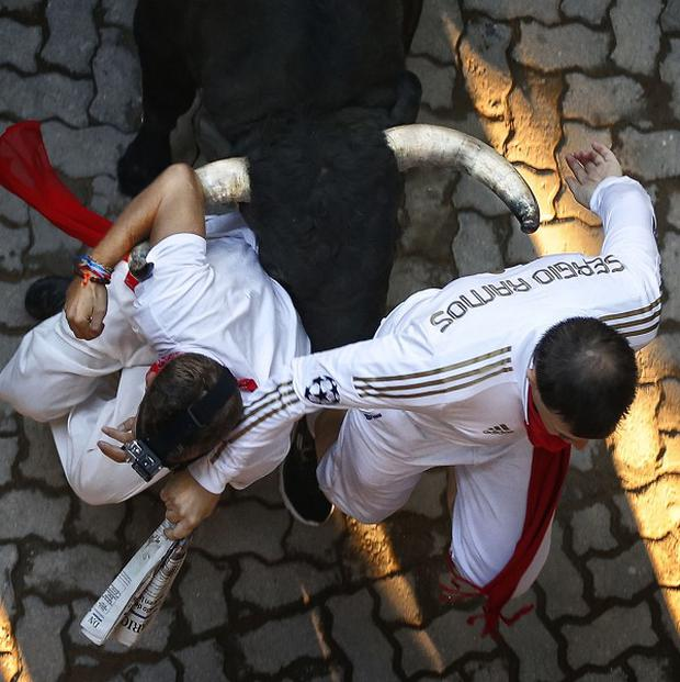 Revellers are chased during the running of the bulls at the San Fermin festival in Pamplona, Spain (AP)