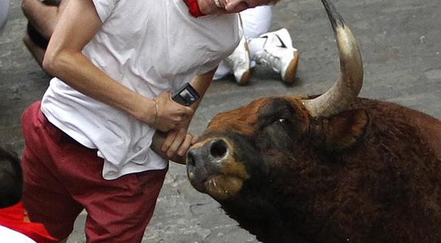 A runner is gored by an El Pilar fighting bull during the running of the bulls at the San Fermin festival in Pamplona, Spain (AP)