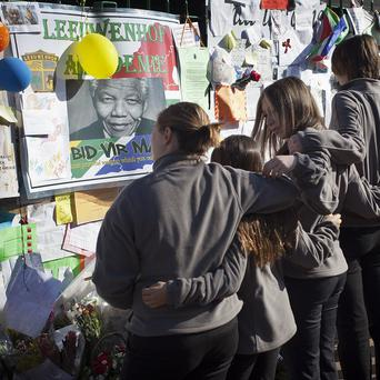 Members of the Toronto Children's Chorus group examine tributes left for Nelson Mandela after singing outside the Mediclinic Heart Hospital in Pretoria (AP)