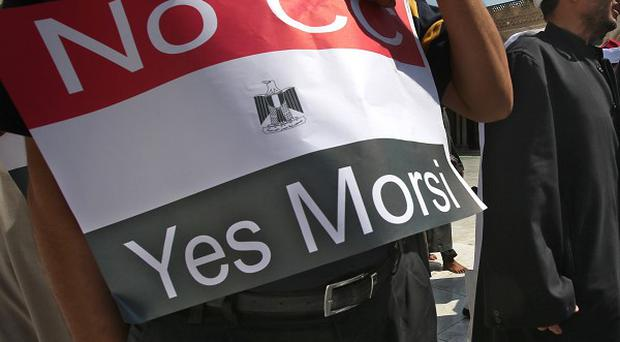 An Egyptian supporter of ousted president Mohammed Morsi holds up a placard in Cairo (AP)