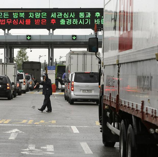 A security officer directs South Korean vehicles as they leave for the joint Kaesong Industrial Complex (AP)