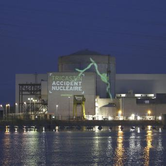A video projection reading 'Tricastin, nuclear accident' on the Tricastin power plant complex in southern France (AP/Greenpeace)