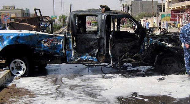 A police officer inspects a police vehicle destroyed by a car bomb attack in Kirkuk (AP)