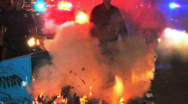 Police officers work to extinguish a fire during a protest after George Zimmerman was found not guilty (AP/Bay Area News Group, Anda Chu)