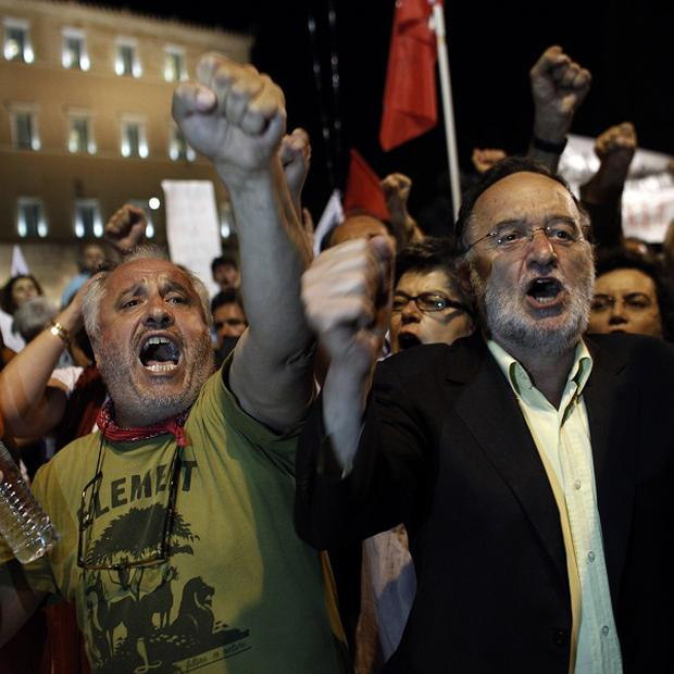 Lawmakers and supporters of the left wing opposition party Syriza shout slogans during a protest in front of the Greek parliament in Athens (AP)