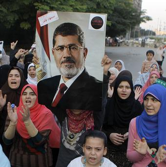 Supporters of Egypt's ousted president Mohammed Morsi hold a protest in a park in front of Cairo University (AP)