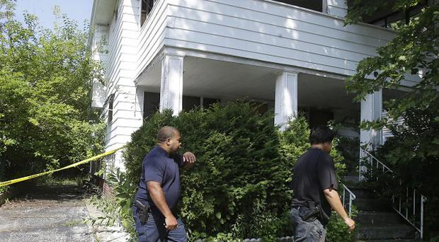 Police search a house where a body was recently found in East Cleveland, Ohio (AP/Tony Dejak)