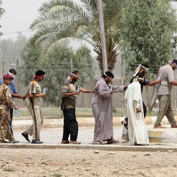 Suspected al-Qaida members are led away to detention centres in Baghdad (AP)
