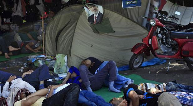 Supporters of Egypt's ousted president Mohammed Morsi sleep on the street where protesters have set up a camp near Cairo University (AP)
