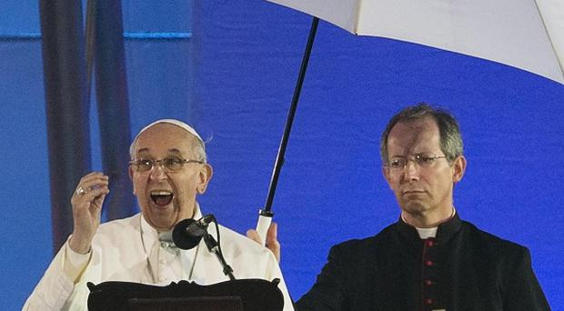 Pope Francis speaks and MC Guido Marini holds an umbrella at the World Youth Day event in Rio de Janeiro, Brazil (AP)