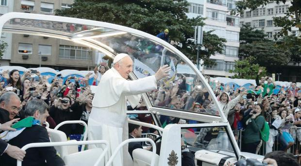 Pope Francis waves from his popemobile as he arrives for the Way of the Cross procession