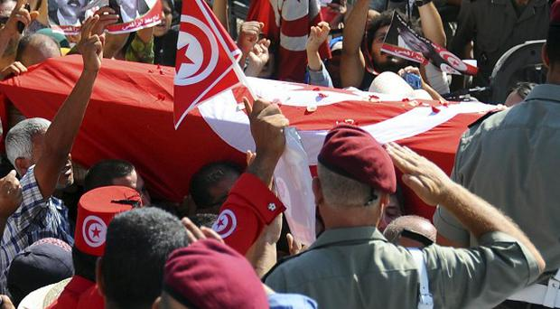 The coffin of Tunisian opposition politician Mohammed Brahmi is carried out of his home in El Ghazela prior to a funerals in Tunis (AP)