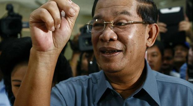 Cambodia's Prime Minister Hun Sen shows his inked finger after casting his ballot at a polling station in Takhmau town, south of Phnom Penh (AP)