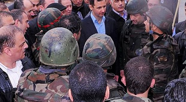 A photo from the official Instagram account of the Syrian Presidency shows Bashar Assad visiting soldiers in Baba Amr, Homs (AP/Syrian Presidency via Instagram)