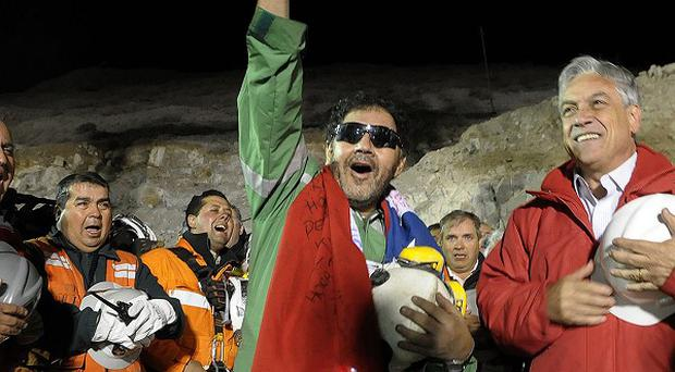 President Sebastian Pinera, right, stands next to the the last miner to be rescued, Luis Urzua, centre, who raises his right fist after his rescue from the collapsed San Jose gold and copper mine (AP)