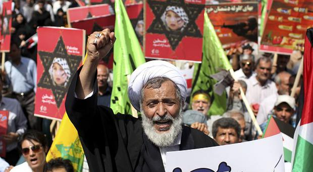 An Iranian cleric holding an anti-Israeli placard chants slogans at an annual pro-Palestinian rally in Tehran (AP)