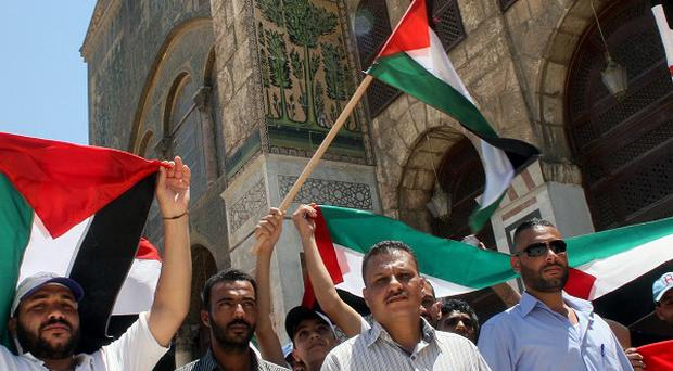 Syrians and Palestinians wave their flags during a festival held inside the Umayyad Mosque in Damascus, Syria (AP)