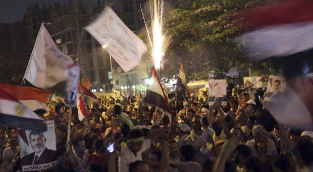 Supporters of Egypt's ousted President Mohammed Morsi wave national flags during a protest near Cairo airport (AP)