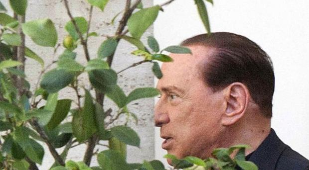 Italian former Premier Silvio Berlusconi walks inside the courtyard of his headquarters in Rome. (AP Photo/Mauro Scrobogna, Lapresse)
