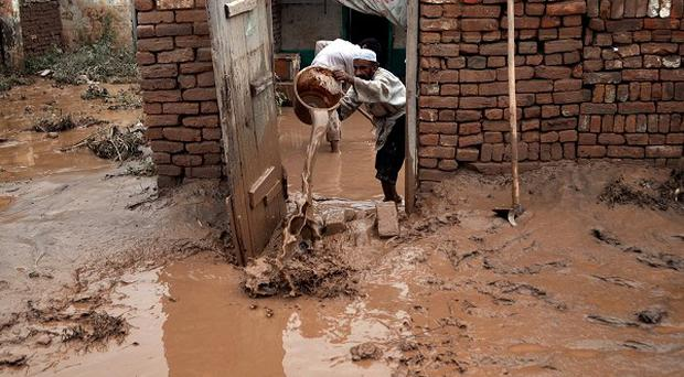 A Pakistani empties a bucket of muddy water from his home after it was flooded by heavy rains in Peshawar (AP)