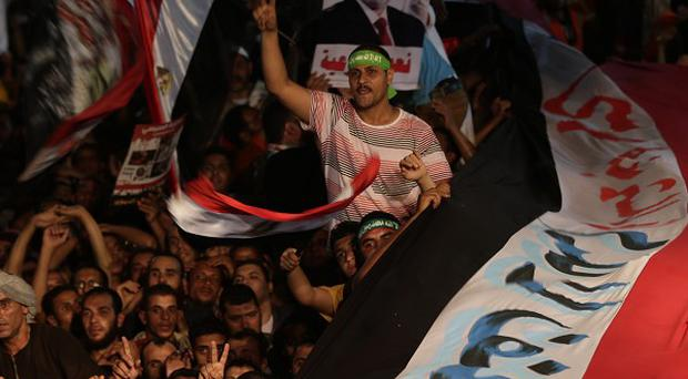 Supporters of Egypt's ousted President Mohammed Morsi hold a large Egyptian national flag as chant slogans (AP)