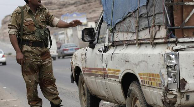 A Yemeni soldier stops a car at a checkpoint in a street leading to the US embassy in Sanaa, Yemen (AP Photo)
