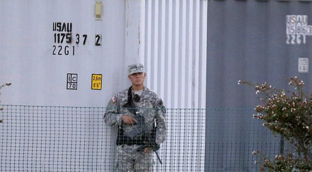 A solider stands guard outside the court martial of Major Nidal Malik Hasan in Fort Hood, Texas (AP)