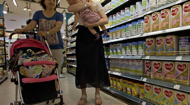 A woman shops for milk powder in a supermarket in Beijing, China (AP)