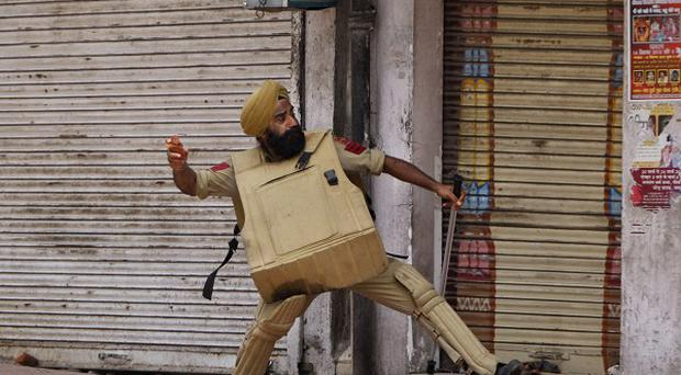 An Indian policeman throws stones at Hindus protesting against the state government after rival communities clashed in Kishtwar, in Jammu (AP)