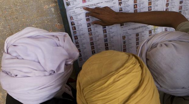 Men search for their names on a list of registered voters outside a polling station in Kidal, Mali (AP)