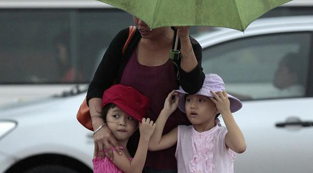 Two girls stay close to their mother during heavy rain in Manila, Philippines (AP/Aaron Favila)