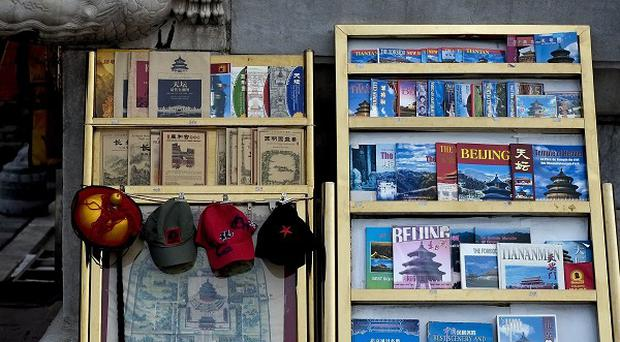 Guidebooks of China's famous tourist spots are sold at the Temple of Heaven in Beijing, although visitor numbers are down (AP)