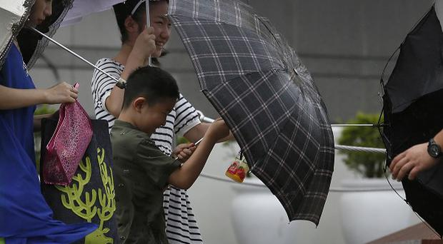 Tourists battle against winds near the waterfront in Hong Kong (AP)