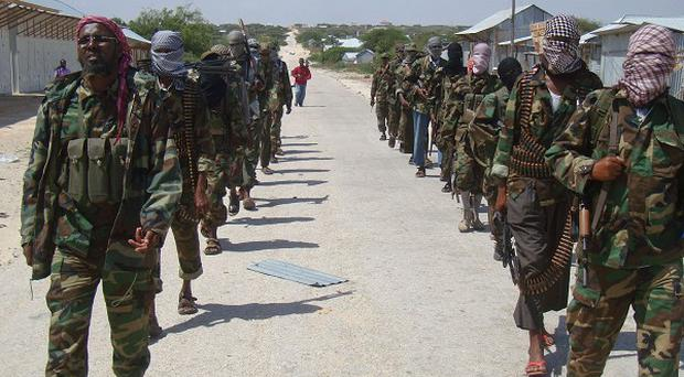 Members of Somalia's al- Shabab militant group patrol on foot on the outskirts of Mogadishu (AP)