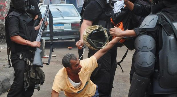 Egyptian security forces detain a supporter of ousted Mohammed Morsi as they clear a sit-in camp set up near Cairo University (AP)