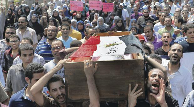Supporters of Egypt's ousted President Mohammed Morsi march towards Old Cairo as they carry the coffin of a colleague