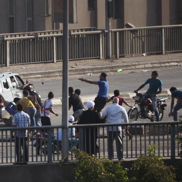 A supporter of ousted president Mohammed Morsi aims his gun at a car driver in Cairo (AP)