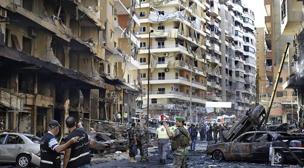 Lebanese army investigators inspect the site of a car bomb explosion (AP)