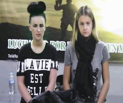 Michaella McCollum Connolly and Melissa Reid stand behind their luggage after being detained at the airport in Lima, Peru